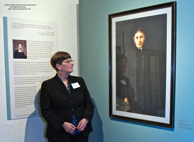Joy M. Kiser Author of American's Other Audubon standing by portrait of Genevieve Estelle Jones at the reception of Nests, Eggs, Heartbreak & Beauty exhibition and book signing, Museum of American Bird Art at Mass Audubon, ©Mardi Welch Dickinson/Kymry GroupAll Rights Reserved.