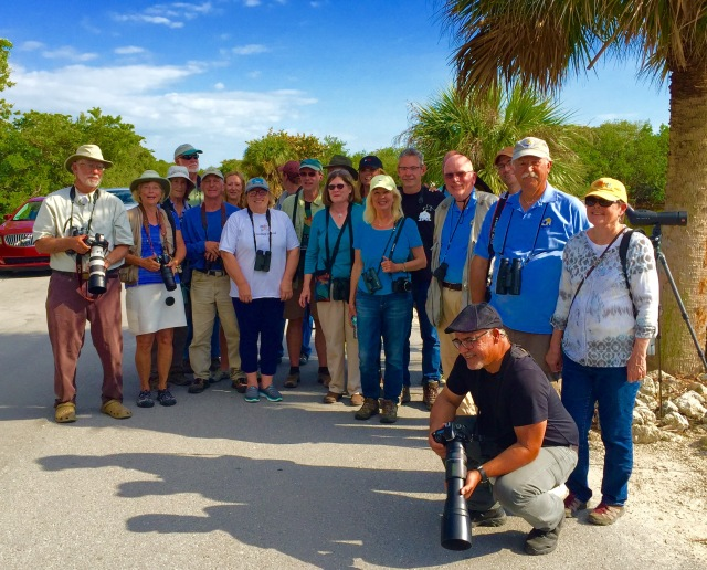 A group of Florida birders and others gathered for a quick pose to celebrate seeing the Great White Pelican, (probable female in breeding plumage), extralimital, roosting with American Pelicans, Ding Darling NWR, Sanibel Island, Florida. ©Mardi Welch Dickinson/ KymryGroup™ All Rights Reserved. Photo may not be used without written permission.